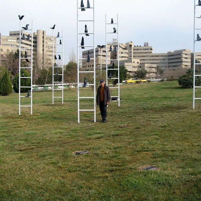 علی داوری در کنار اثرش با عنوان داستان کلاغ ها