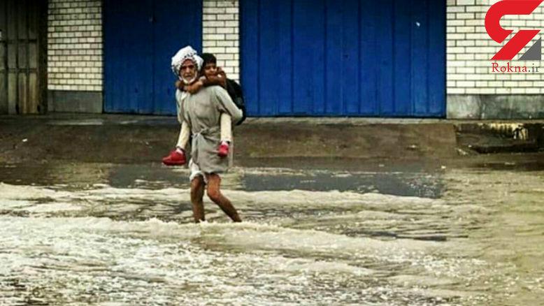 عکسی جنجالی از جابجا کردن دانش آموز اهوازی توسط پدربزرگش در شهر پر از آب